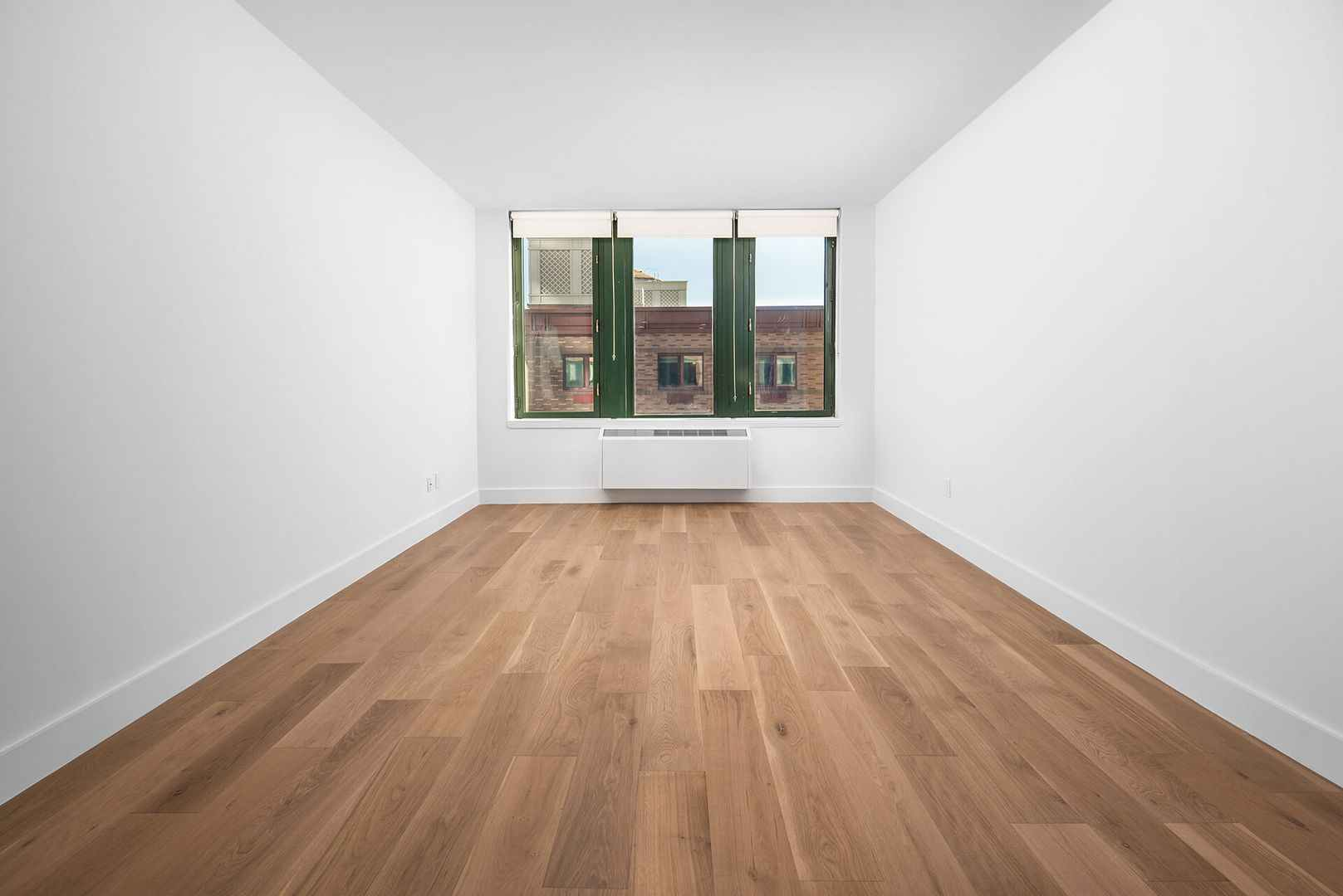 Empty room with wood-plank flooring