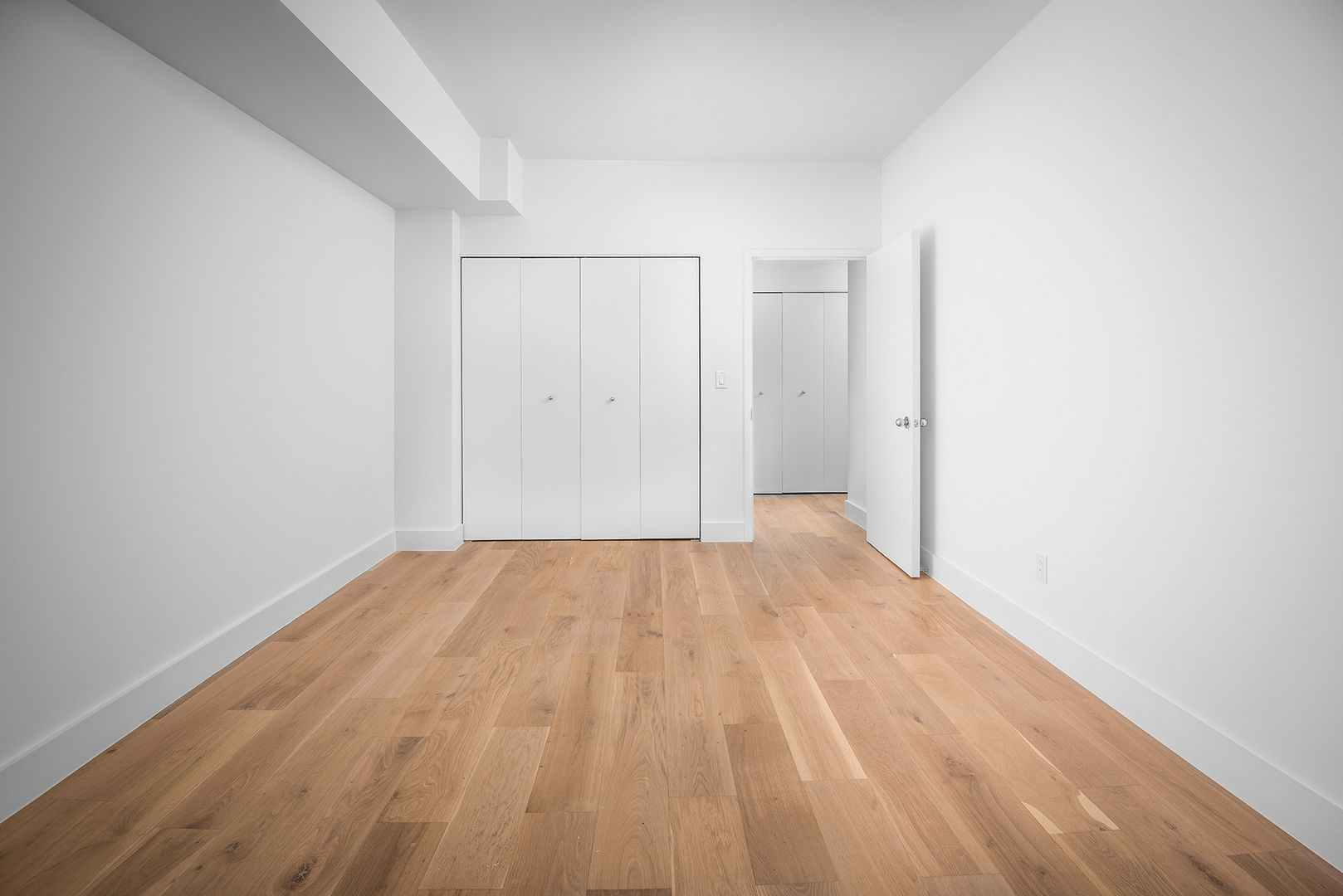 Empty bedroom with large closet and wood plank flooring